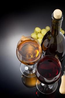 검은 배경에 와인과 와인잔