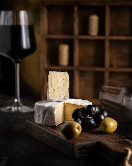 Закуска к вину: сыр, оливки и виноград на столе рядом с бокалом красного вина. фото высокого качества