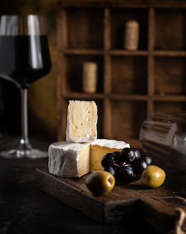 Wine appetizer: cheese, olives and grapes are on the table next to a glass of red wine. high quality photo