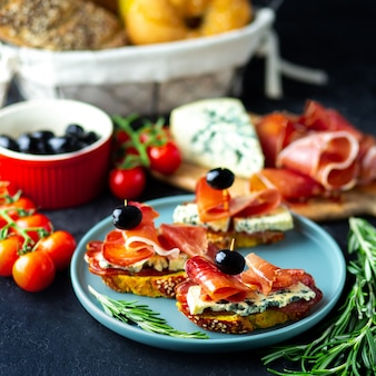 Винная закуска на деревянной доске. белое вино, сыр, хамон, прошутто, с салями и оливками на черном фоне. свежеиспеченный хлеб с сыром и винными закусками. вкусные закуски к вечеринке