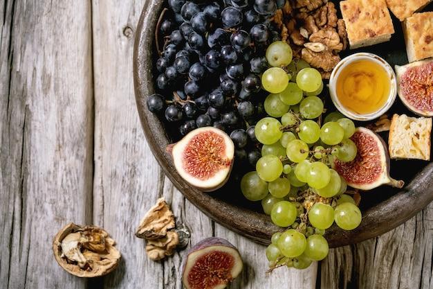 古い木製の背景の上にセラミックプレート上のさまざまなブドウ、イチジク、クルミ、パン、蜂蜜、山羊のチーズとワインの前菜。フラットレイ、コピースペース