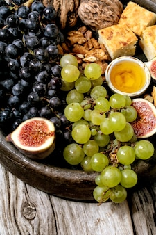 Wine appetizers with different grapes, figs, walnuts, bread, honey and goat cheese on ceramic plate over old wooden background. close up