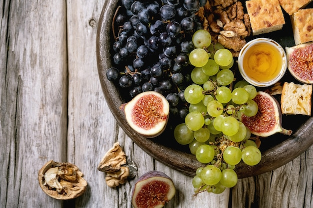 Wine appetizers with different grapes, figs, walnuts, bread, honey and goat cheese on ceramic plate over old wooden background. flat lay, copy space