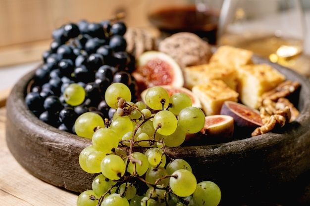 Wine appetizers with different grapes, figs, walnuts, bread, honey and goat cheese on ceramic plate, serving with glasses of red and white wine over old wooden background. close up