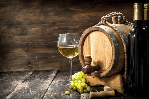 ワインの背景。緑のブドウの枝を持つ白ワインの樽。