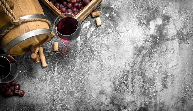 Винный фон. бочка с красным вином и свежим виноградом. на деревенском фоне.