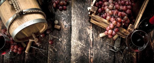 ワインの背景。赤ワインと新鮮なブドウが入った樽。