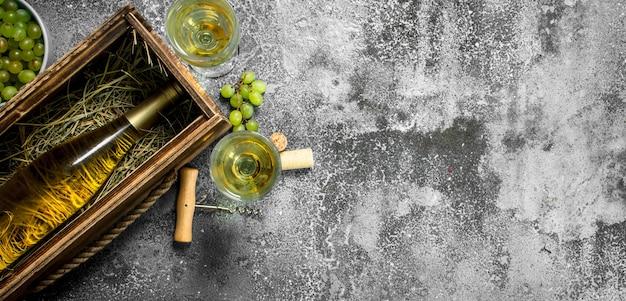 와인 배경. 오래 된 상자에 화이트 와인 한 병. 소박한 배경.