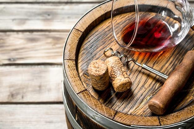 ワインの背景。古い樽に赤ワインを一杯。木製の背景に。