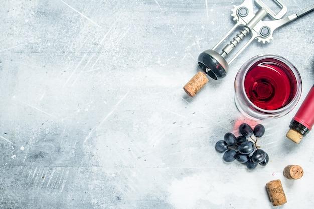 ワインの背景。ブドウと赤ワインのグラス。素朴な背景に。