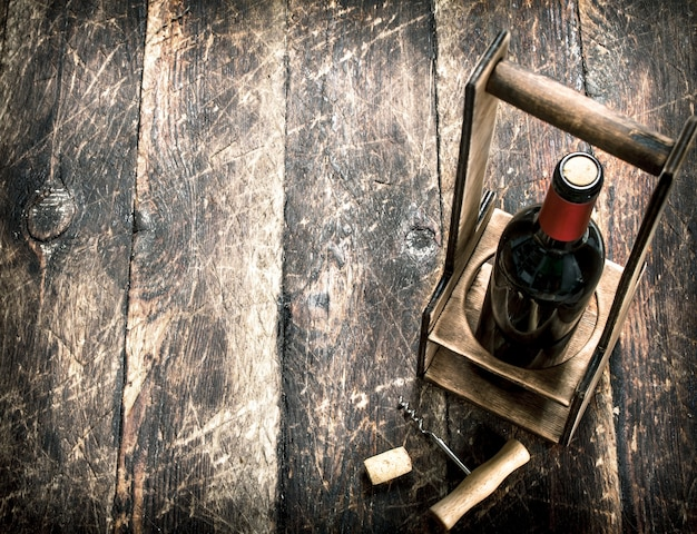 Wine background a bottle of red wine on a stand with a corkscrew on a wooden background
