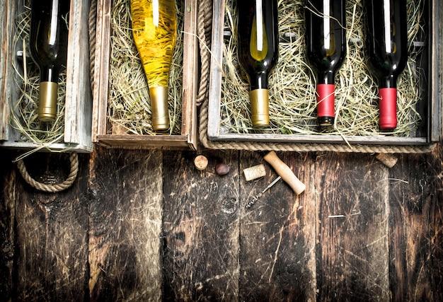 ワインの背景。古い箱に入った赤と白のワインのボトル。木製の背景に。