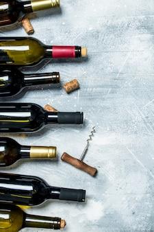 ワインの背景。赤と白ワインのボトル。素朴なテーブルの上。