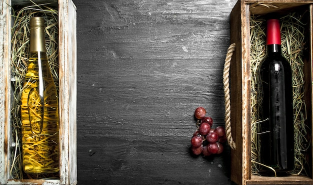 Wine background. bottles of red and white wine in boxes. on the black chalkboard.