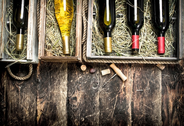 Wine background. bottles of red and white wine in old boxes. on a wooden background.
