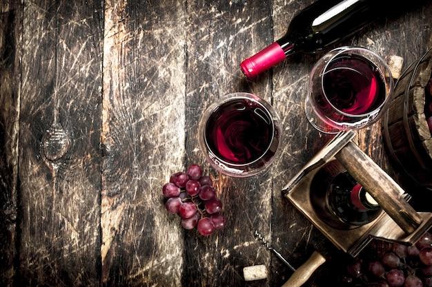 ワインの背景。ブドウとグラスと赤ワイン。木製の背景に。
