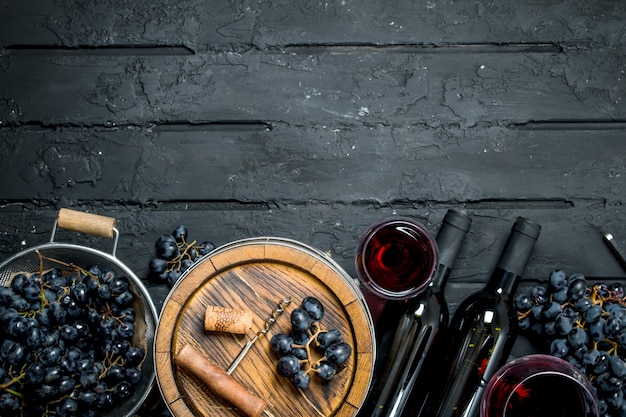 ワインの背景。ブドウと古い樽の赤ワイン。黒の素朴な背景に。
