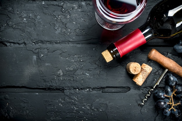 ワインの背景。ブドウと栓抜きの赤ワイン。黒の素朴な背景に。