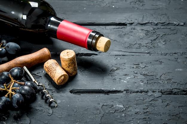 ワインの背景。ブドウと栓抜きの赤ワイン。黒い素朴なテーブルの上。