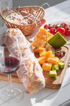 Wine, baguette and cheese on wooden table