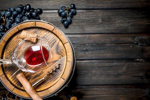 Вино. бочка с красным вином и виноградом. на деревянном.