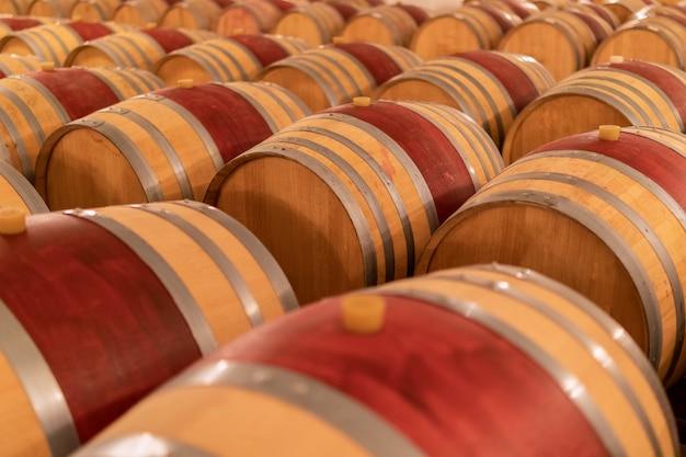 Винные бочки сложены в старом погребе винодельни.