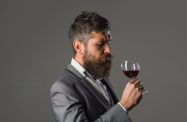 Wine bearded man with glass of wine tasting alcohol red wine man with alcohol man in suit drinks