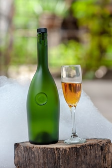 Wine bottle and champagne glass with white bubbles background