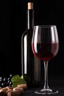 Wine bottle and glass of red wine on dark textured surface