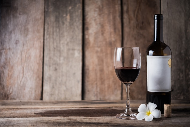Wine bottle, glass and white flower on wood background