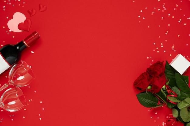 ワインボトル、グラス、赤い背景の上のギフトボックスと花のバラ