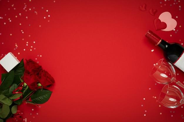 와인 병, 안경, 빨간색 배경에 선물 상자 꽃 장미