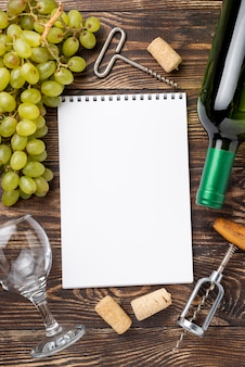 Wine bottle and grapes beside notebook