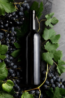 Wine bottle grapes, grape bunches with leaves and vines corkscrew on dark rustic concrete background. flat lay wine composition on black stone table.