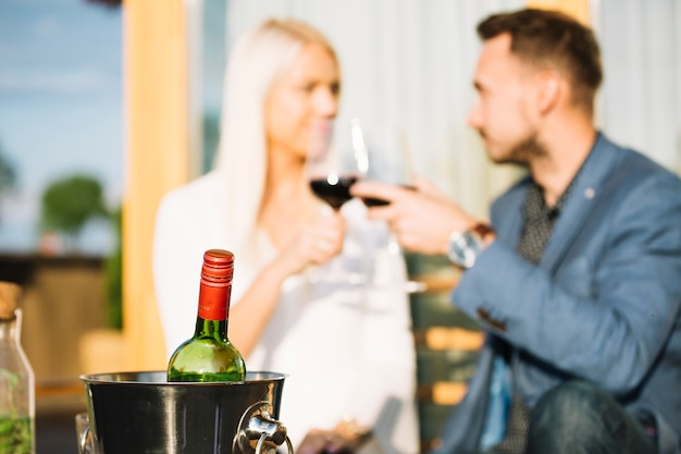 Wine bottle in ice bucket with couple toasting wine glasses