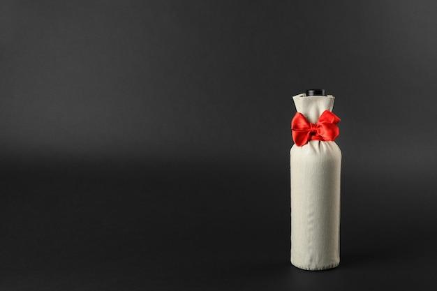 Бутылка вина в подарочной сумке на темном фоне