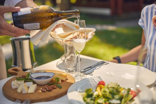 Бутылка вина в мужских руках и тарелки с вкусной едой