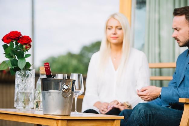 一緒に座ってカップルの前に氷のバケツの中にワインボトル