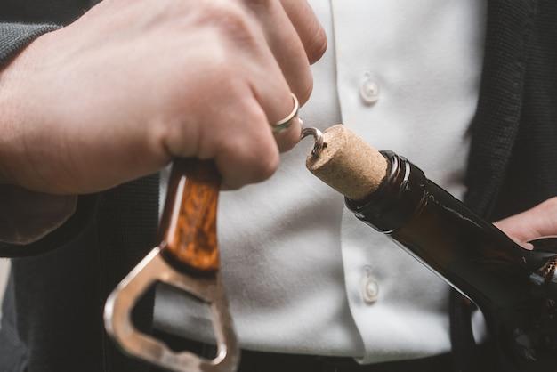 Открытие винной бутылки. руки и штопор.