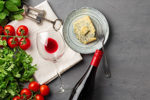 Wine bottle and plate of cheese on gray surface flat lay top view