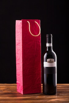 Wine bottle and red paper bag on wooden table against black backdrop