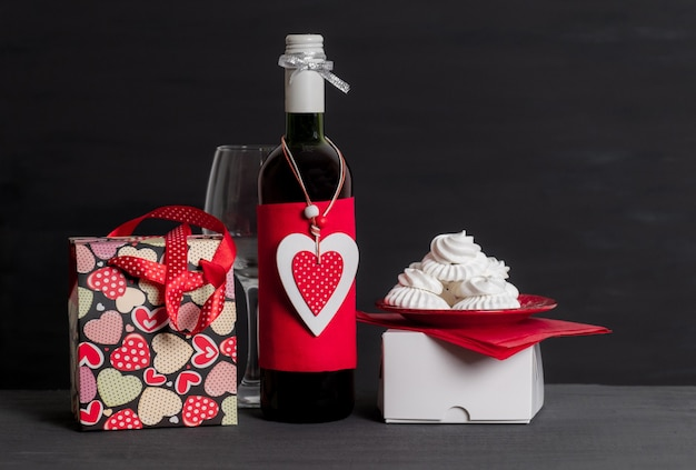 Wine bottle, shopping bag, white box and red heart of valentine's day on black