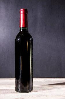 暗闇の中で木製のテーブルの上に立ってワインボトル