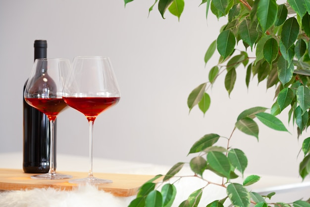 Wine bottle and two burgundy glasses red wine on wooden table on white background