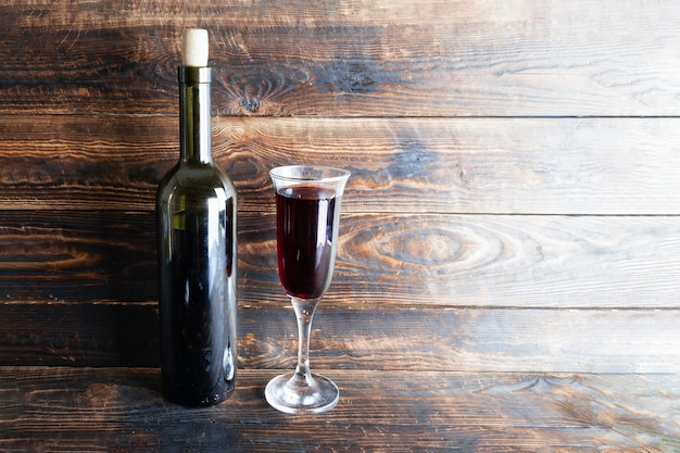 Wine bottle and wine glass on wooden plank surface.