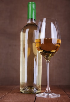 Wine bottle and wineglass with white wine on wooden