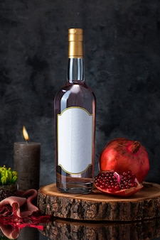 Wine bottle with candle, pomegranate, plant and scarf on a wooden piece