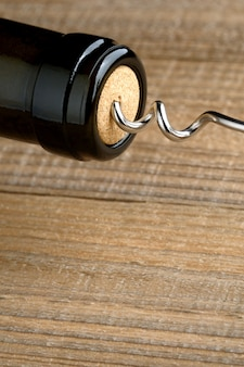 Wine bottle with corkscrew closeup on wood