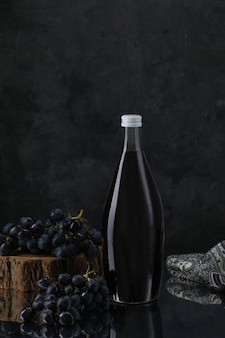 Wine bottle with grapes on wooden piece and scarf
