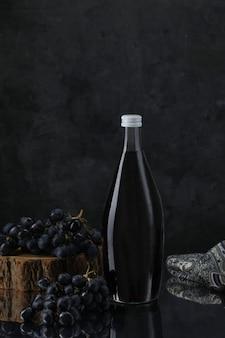 Bottiglia di vino con uva su pezzo di legno e sciarpa